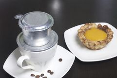 Vietnamese coffee maker is equipped on a cup. It is filled with ground coffee and pour boiling water. There is a cake on the sauce. R Stock Photo
