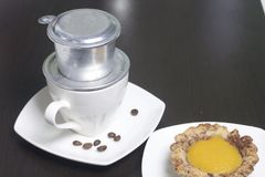 Vietnamese coffee maker is equipped on a cup. It is filled with ground coffee and pour boiling water. There is a cake on the sauce. R Royalty Free Stock Photos