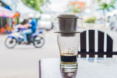 Vietnamese coffee in a street cafe on the background of a road Stock Image