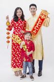 Vietnamese couple holding good luck item for new year. Vietnamese couple wear red to celebrate lunar new year smiling with the ang bao and hangings Stock Photography
