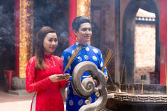 Vietnamese couple with incense sticks. Young couple with incense sticks standing in front of urn in the temple stock images