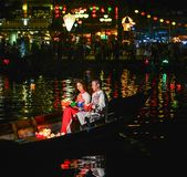 Vietnamese couple sitting on wooden boat stock photography