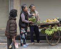 Vietnamese die straatventer in Hanoi, met fiets met bananen wordt geladen royalty-vrije stock foto's
