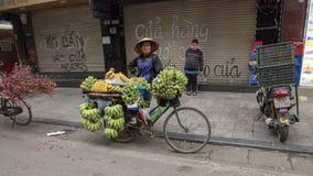 Vietnamese die straatventer in Hanoi, met fiets met bananen wordt geladen stock fotografie