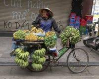 Vietnamese die straatventer in Hanoi, met fiets met bananen wordt geladen stock afbeeldingen