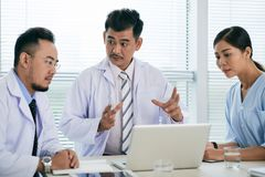 Conducting meeting. Vietnamese doctor conducting meeting with coworkers in his office Royalty Free Stock Photography
