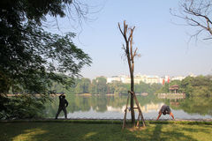 Vietnamese doing their morning exercise at Hoan Kiem Lake. Royalty Free Stock Photo