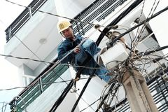 Free Vietnamese Electricity Worker Climb High On Electric Post To Repair Electricity Network Stock Photo - 153562860