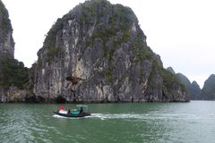 Vietnamese family operating a small boat selling fruit to tourists on ha long bay Vietnam Stock Photos