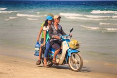Vietnamese Family Rides Motorbike on Sand Ocean Beach. NHA TRANG/VIETNAM - APRIL 16 2017: Vietnamese family ride old motorbike on ocean sand beach against wave Royalty Free Stock Images