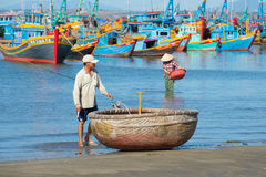 Vietnamese fisherman at the national round boats on the bank sea Royalty Free Stock Images
