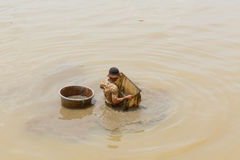 A vietnamese fisherman is searching for shells in the water Royalty Free Stock Photo