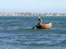 Vietnamese fisherman on traditional round wicker boat Thung chai fishing in the Bay of Mui Ne Royalty Free Stock Images