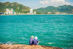 Vietnamese fishermen sitting on the edge of a cliff and fishing. royalty free stock photography