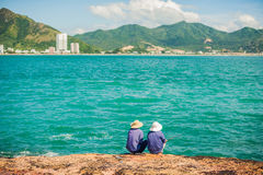 Vietnamese fishermen sitting on the edge of a cliff and fishing. royalty free stock photo