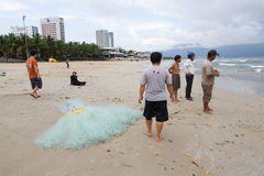Vietnamese fishermen stand by beach in Danang City observing, preparing Royalty Free Stock Photos