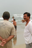 Vietnamese fishermen stand by the beach in Danang City observing Royalty Free Stock Photography