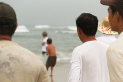 Vietnamese fishermen stand by the beach in Danang City observing Stock Photo