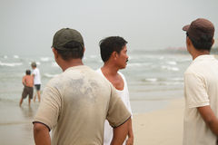 Vietnamese fishermen stand by the beach in Danang City observing Stock Images