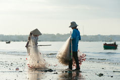 Vietnamese fishers (man and woman) fold nets Stock Photos