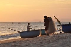 Vietnamese fishers at work with fishing nets at sunset Stock Photos