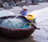Vietnamese fisherwoman with conical hat check her nets for the catch fish from the beach. In vietnamn royalty free stock photography