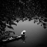 Vietnamese Fishing. Blackandwhite boat Vietnam reflections on still water Royalty Free Stock Photography