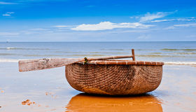 Vietnamese Fishing Boat. A handmade round fishing boat sits on the beach in Vietnam Stock Photos