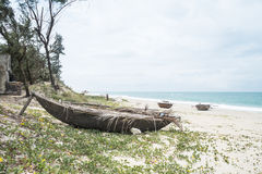 Vietnamese fishing boat on a secluded beach in Hoi An. Photo of a vietnamese-style fishing boat laid to rest on one of Hoi An`s secluded beaches Royalty Free Stock Images