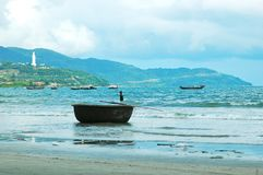 Vietnamese fishing boats near a beach, with a giant white statue overlooking them. Traditional Vietnamese fishing boats near a beach, with a basket-shaped boat Stock Photos