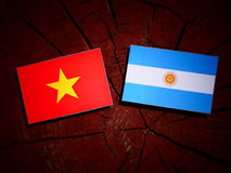 Vietnamese flag with Argentinian flag on a tree stump  Stock Photography