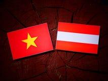 Vietnamese flag with Austrian flag on a tree stump  Royalty Free Stock Photo