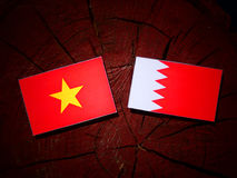 Vietnamese flag with Bahraini flag on a tree stump isolated Stock Image