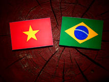 Vietnamese flag with Brazilian flag on a tree stump isolated Stock Image