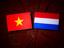 Vietnamese flag with Dutch flag on a tree stump isolated Royalty Free Stock Photos