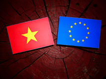 Vietnamese flag with EU flag on a tree stump isolated. Vietnamese flag with EU flag on a tree stump Stock Photo