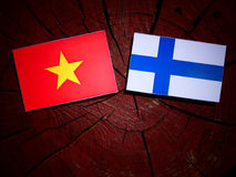 Vietnamese flag with Finnish flag on a tree stump isolated Royalty Free Stock Photos
