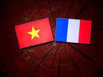 Vietnamese flag with French flag on a tree stump isolated Royalty Free Stock Photos