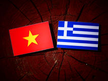 Vietnamese flag with Greek flag on a tree stump isolated Royalty Free Stock Image