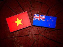 Vietnamese flag with New Zealand flag on a tree stump isolated Royalty Free Stock Images