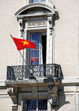 Vietnamese Flag Ornate Window. A colorful red and yellow flag flies from the balcony of an ornate building Royalty Free Stock Photo