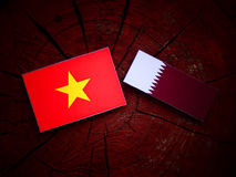 Vietnamese flag with Qatari flag on a tree stump isolated Royalty Free Stock Photo