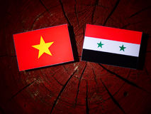 Vietnamese flag with Syrian flag on a tree stump isolated Stock Photo