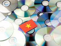 Vietnamese flag on top of CD and DVD pile isolated on white. Vietnamese flag on top of CD and DVD pile isolated Royalty Free Stock Images