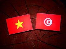 Vietnamese flag with Tunisian flag on a tree stump isolated. Vietnamese flag with Tunisian flag on a tree stump Stock Photography