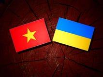 Vietnamese flag with Ukrainian flag on a tree stump isolated. Vietnamese flag with Ukrainian flag on a tree stump Royalty Free Stock Photography