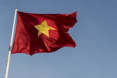 Vietnamese flag waving in the wind on a pole. Against a blue sky background Royalty Free Stock Photography