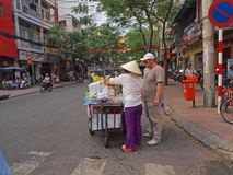 Vietnamese Fruit Seller. Female hawker selling freshly cut fruits to a tourist Royalty Free Stock Photos