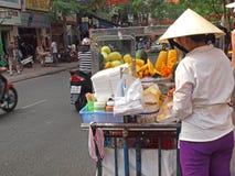 Vietnamese Fruit Seller. Female hawker selling freshly cut fruits on a pushcart Royalty Free Stock Image
