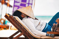 Vietnamese fruits saleswoman resting on a lounger on the beach Stock Image